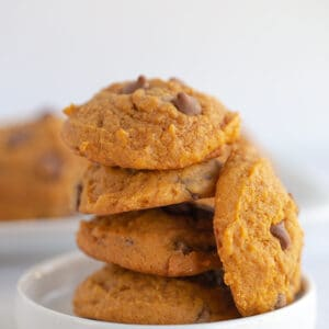 pumpkin chocolate chip cookies stacked on a small white dessert plate with a platter of cookies behind it