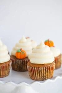 pumpkin cupcakes with swirls of frosting on a wavy white cake plate