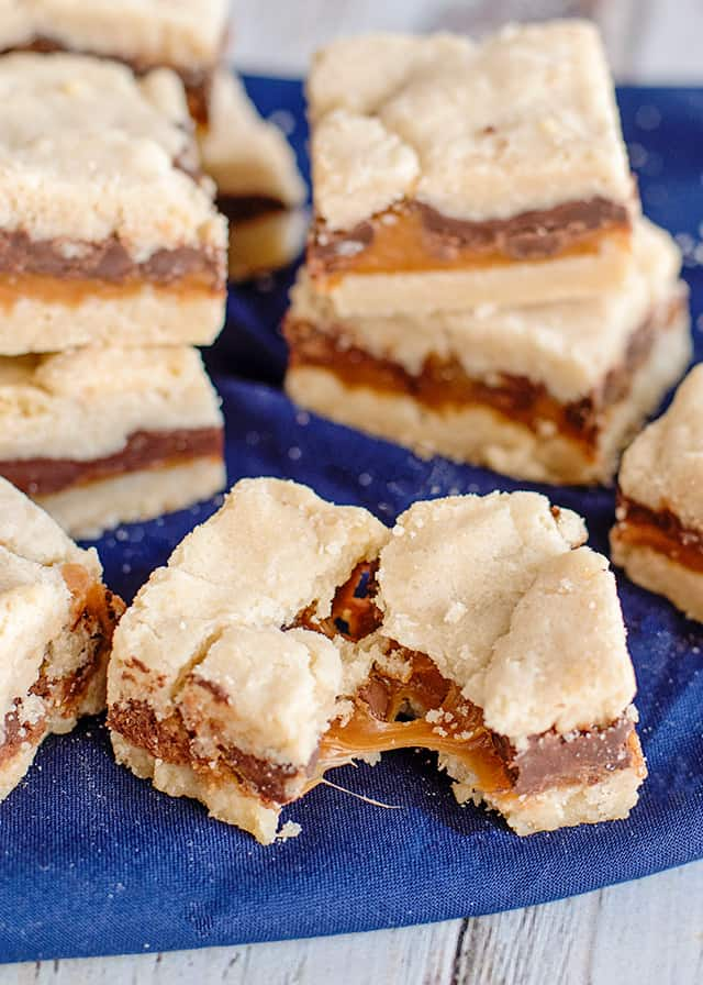 shortbread bars broke in half with the gooey caramel stretching out of it on a blue fabric