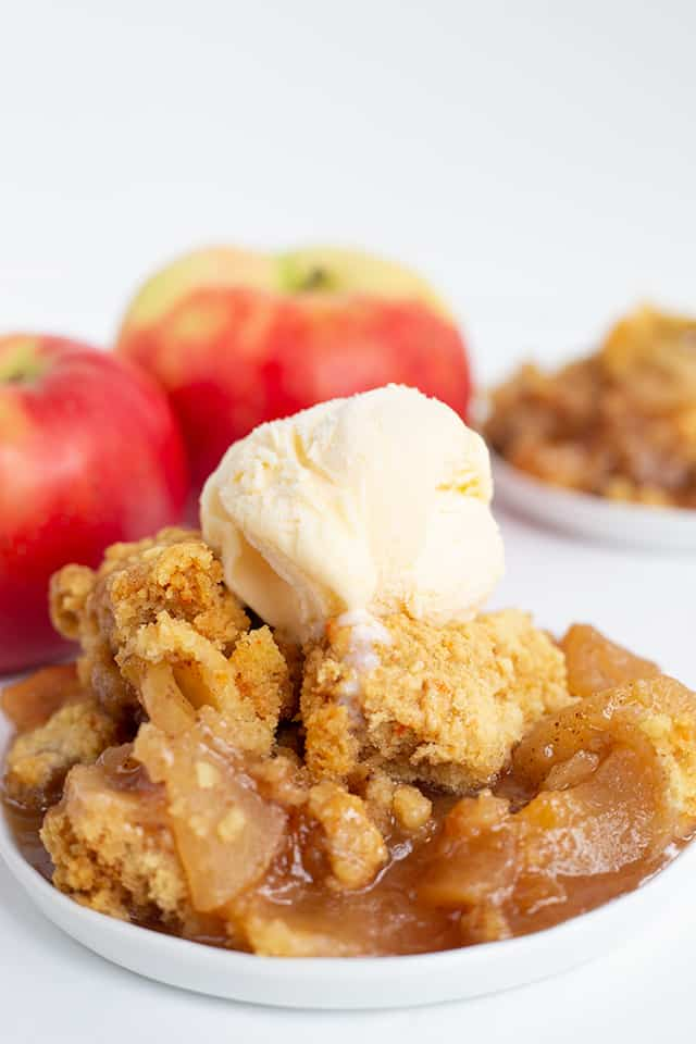 white plate full of slow cooker apple cobbler with vanilla ice cream on top