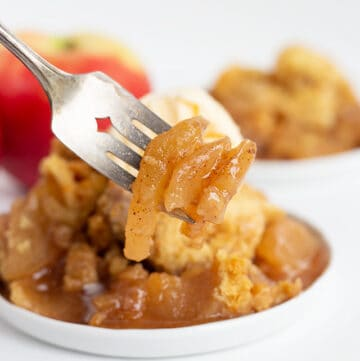 apples on a fork with a plate full of crockpot apple cobbler behind it