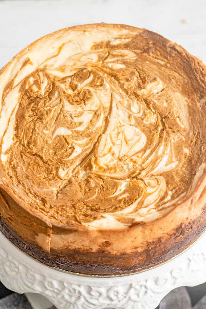 close up of baked pumpkin swirled cheesecake on a white cake plate