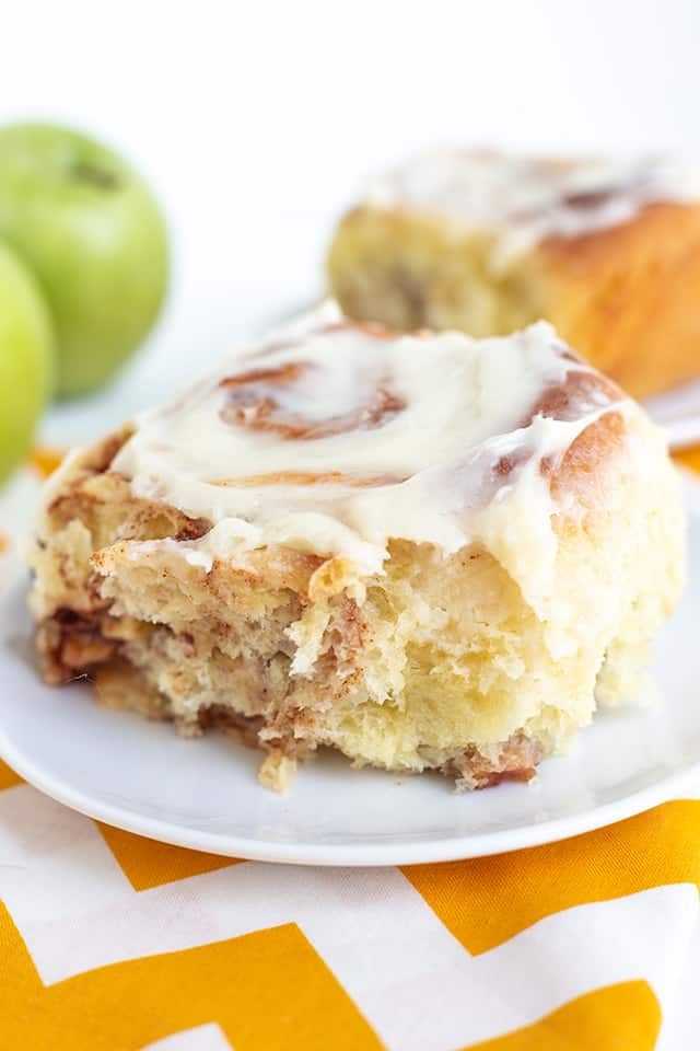 cinnamon roll on a white plate with a yellow and white fabric under it and apples behind the roll
