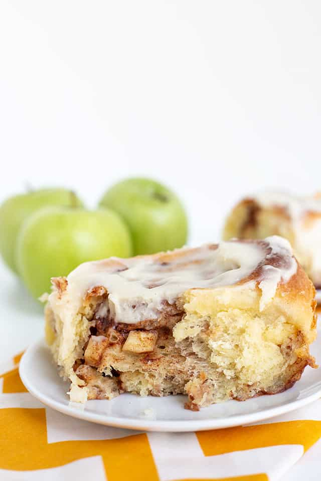 cinnamon roll on a white dessert plate with apples poking out of the cinnamon roll