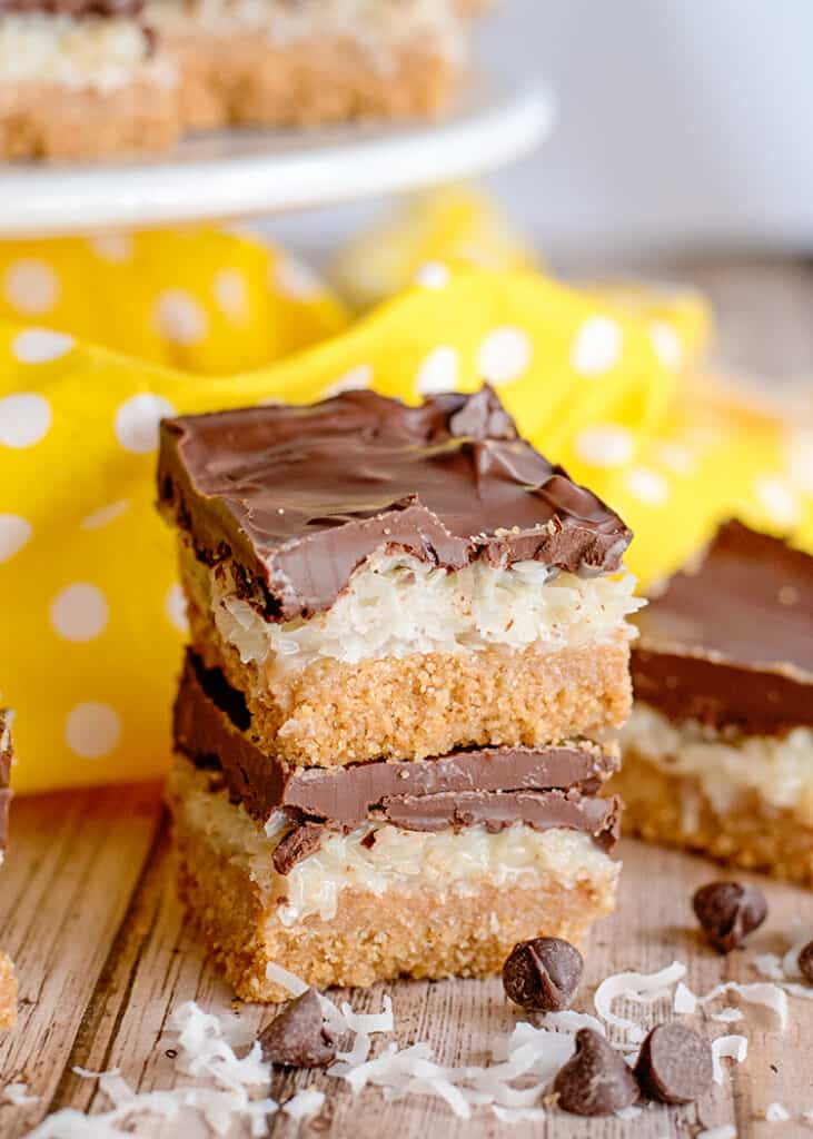 a stack of two bars with coconut and chocolate chips in front of it