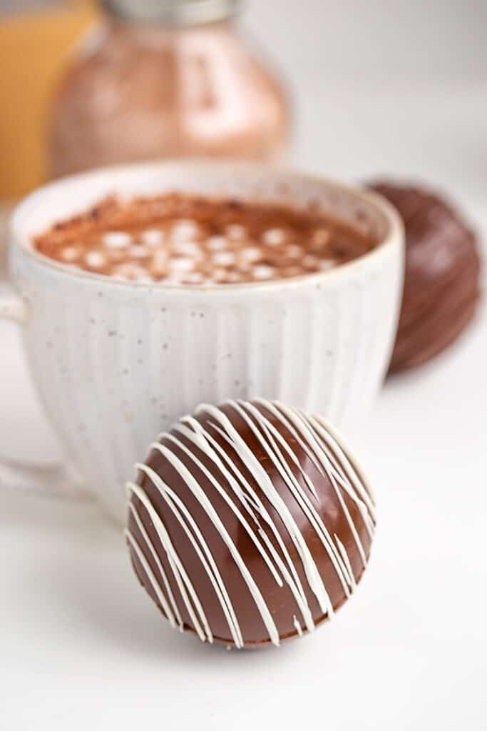 hot chocolate bomb in front of a white mug filled with hot cocoa