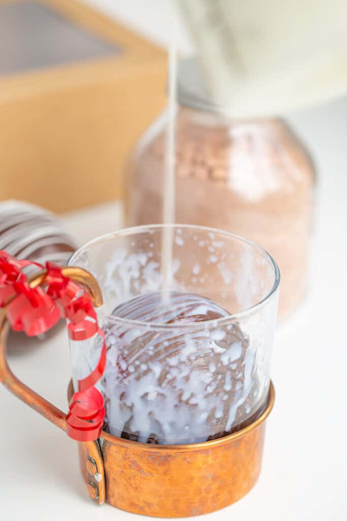 pouring hot milk on a hot chocolate bomb in a clear glass with a copper bottom