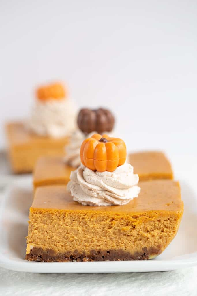 two slices of pumpkin cheesecake bars on white plates with pumpkins on top