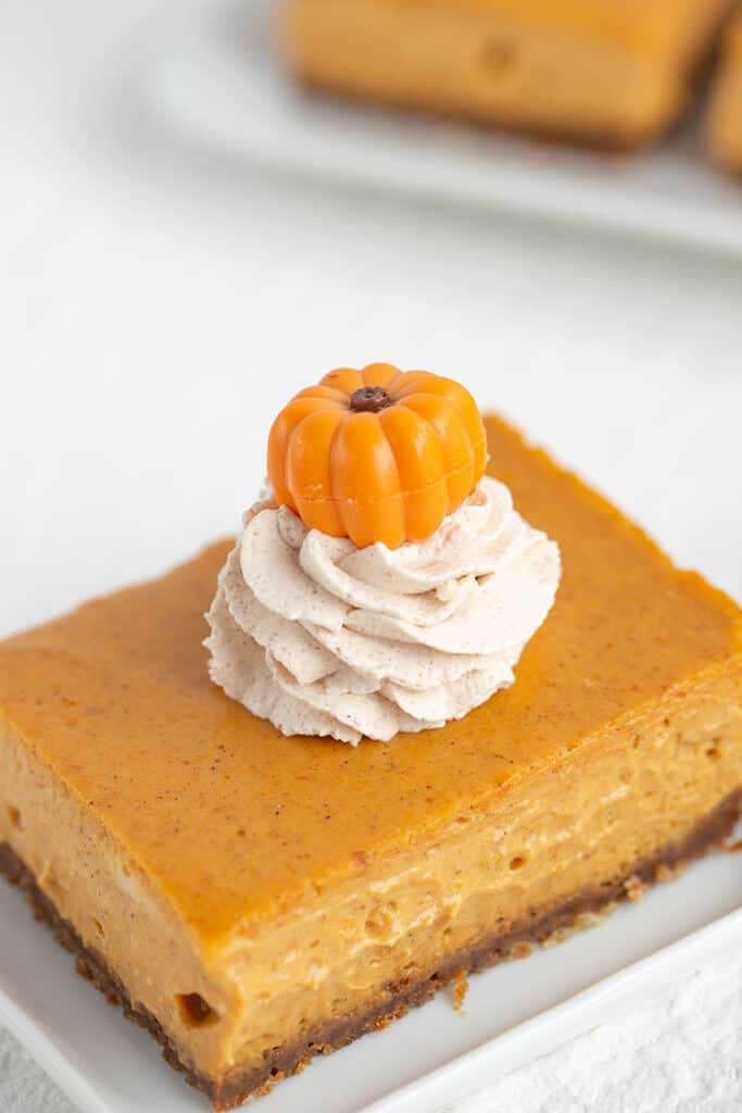 cheesecake bars showing the pumpkin truffle on top of the whipped cream that's sitting on the pumpkin bar