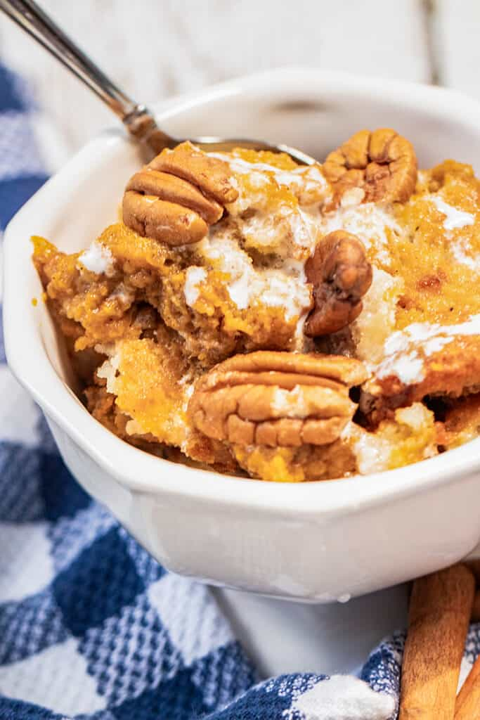 white bowl full of pumpkin pecan cobbler with marshmallow glaze drizzled on top and a blue and white checkered fabric by the bowl
