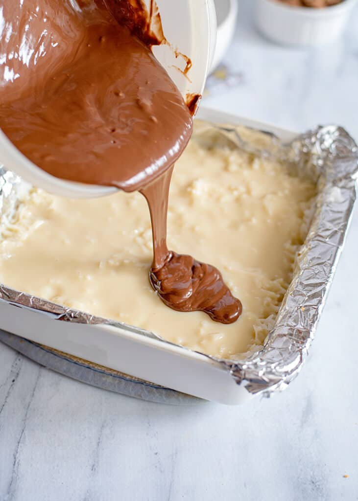 pouring melting chocolate on the sweetened condensed milk and coconut layer of the bars