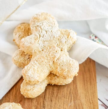 gingerbread dog treats on a cutting board with a white linen under the cookies