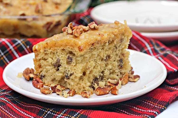 close up horizontal photo of the butter pecan cake on a white plate with plaid fabric under it