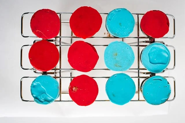 blue and red bottoms of cones on a ice cream cone baking rack on a white surface