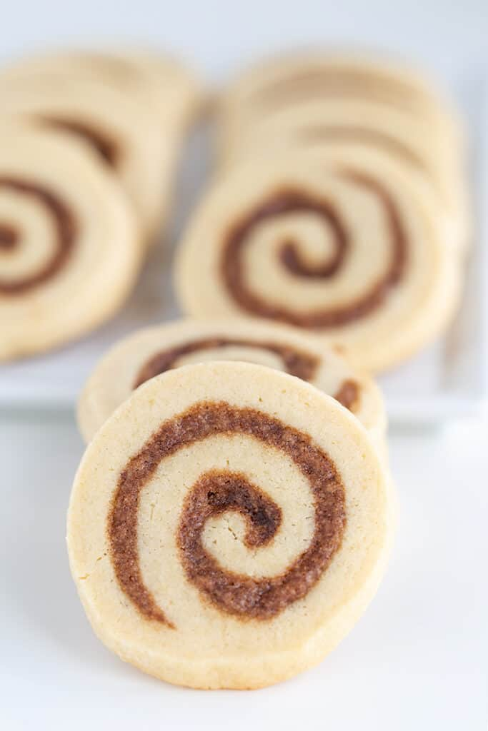 up close photo of the cinnamon roll cookies with a platter of cookies behind it