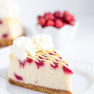 cheesecake on a white lace plate with cranberries behind the cheesecake
