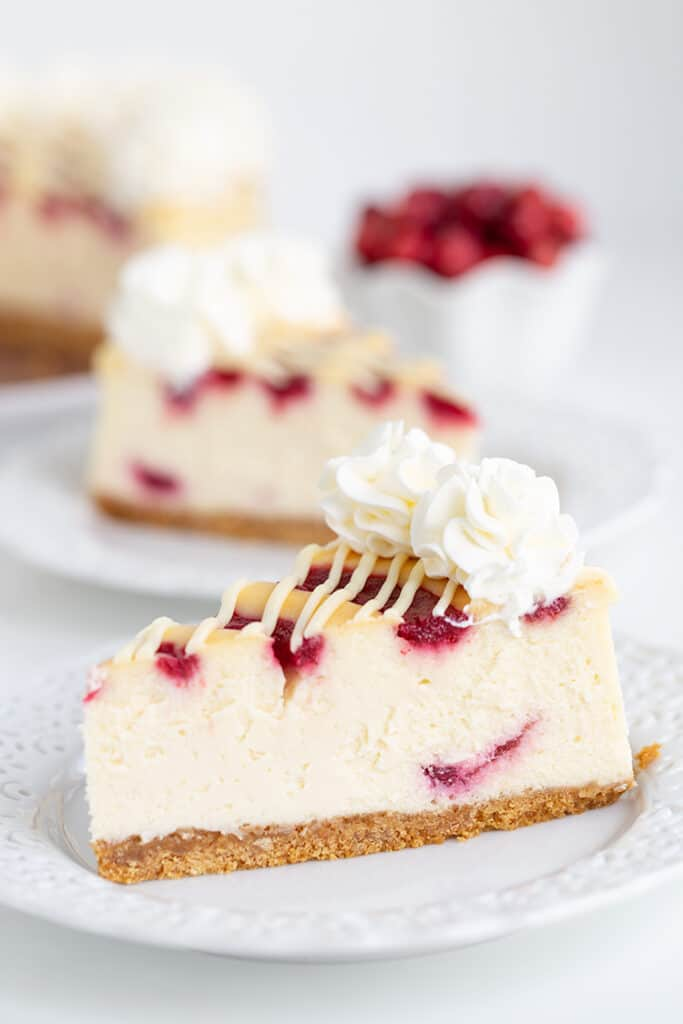 Slice of cheesecake on a white plate with a second slice behind it and cranberries