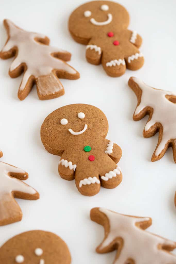 gingerbread men and christmas tree cookies on a white surface
