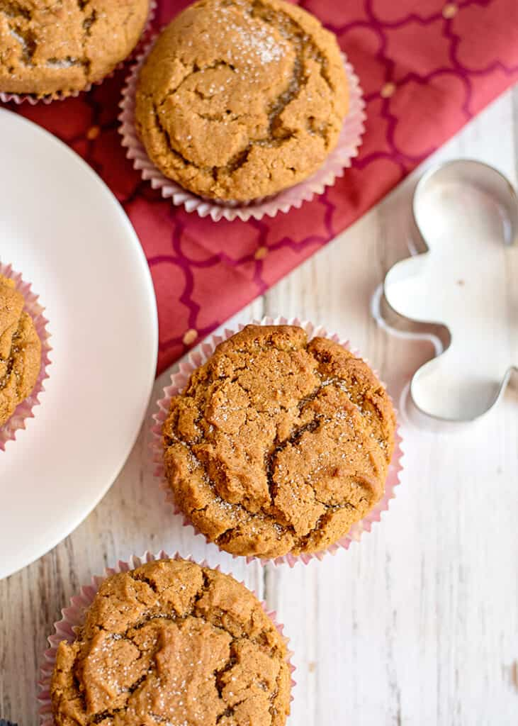 overhead photo of muffins on a white surface with a maroon fabric
