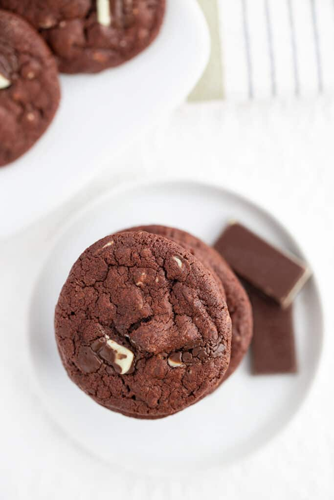 overhead photo of chocolate cookie with chocolate mints beside it on a white surface