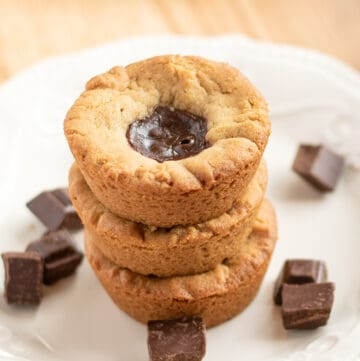 stack of cookie cups with showing the cookie tops with the ganache on a white plate with pieces of chocolate