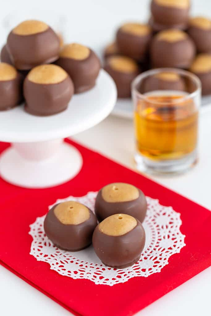 whiskey balls sitting on a doily on a red fabric with a shot glass behind it