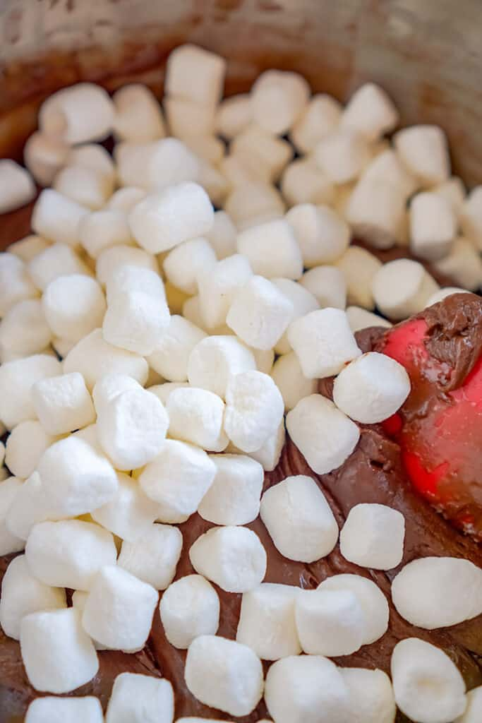 marshmallows being added to a bowl of ingredients