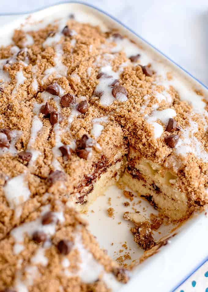 coffee cake in a white square pan with a piece missing