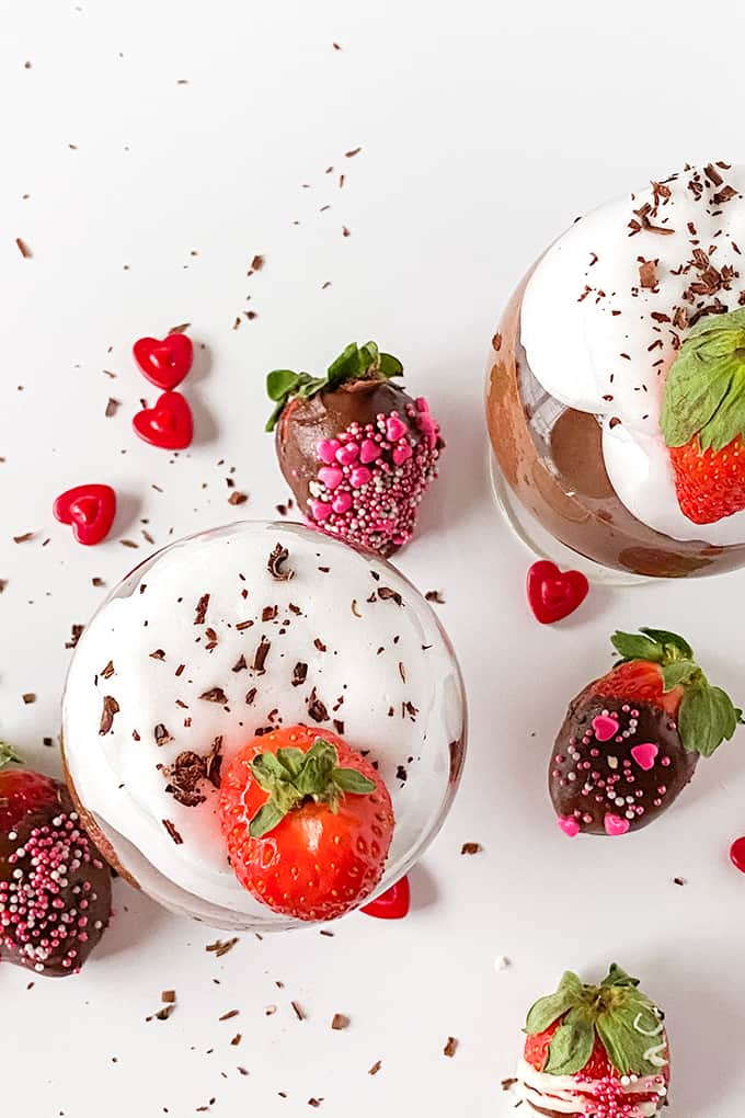 overhead photo of chocolate mousse in glasses with whipped and a strawberry on top on a white surface