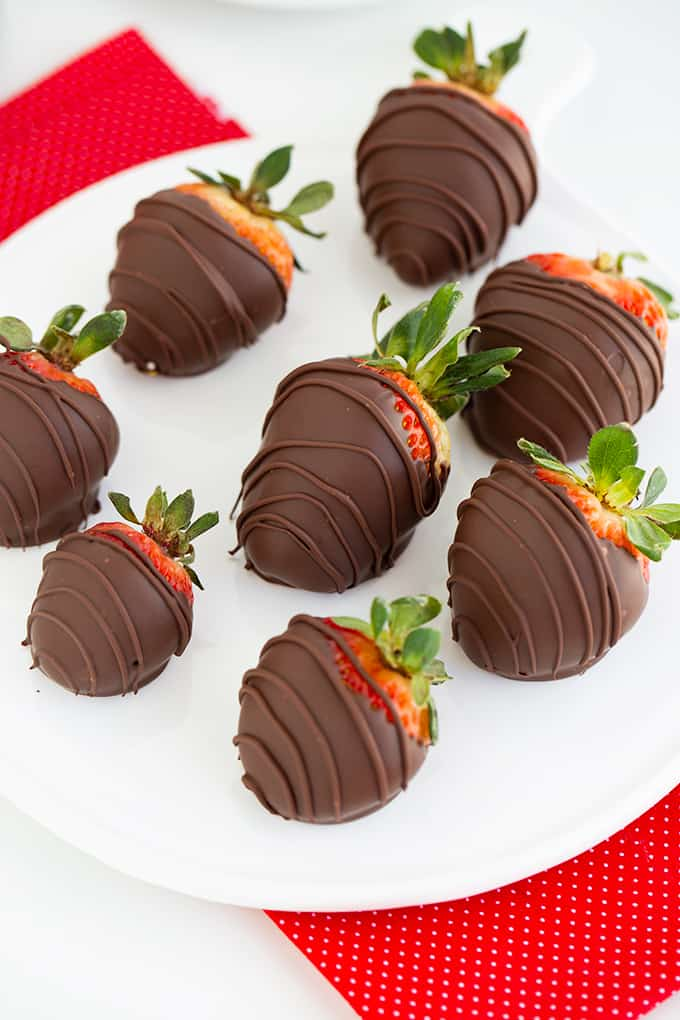 overhead photo showing the chocolate covered strawberries in the center of the platter with a red fabric