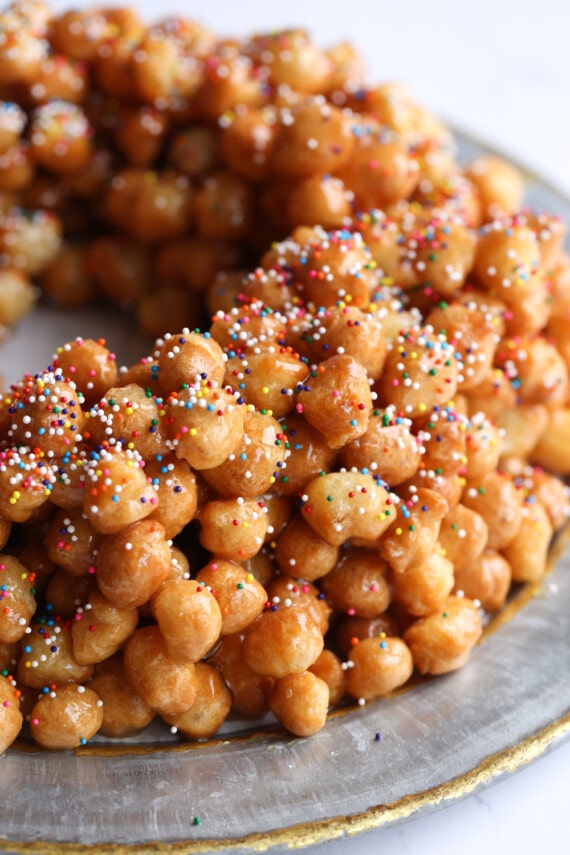Struffoli with Rainbow Sprinkles Arranged in a Wreath Shape on a Plate
