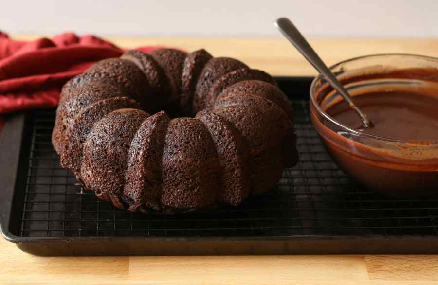 chocolate bundt cake on a cooling rack with ganache in a bowl