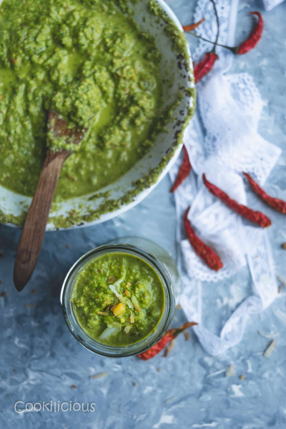 top shot of half a bowl with a wooden spoon and a bottle both filled with Indian Green Chutney with Leftover Lettuce Leaves