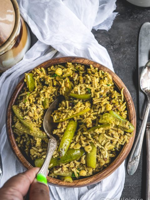 A spoon digging into a bowl of Tendli Masala Bhaat | Ivy Gourd Masala Rice