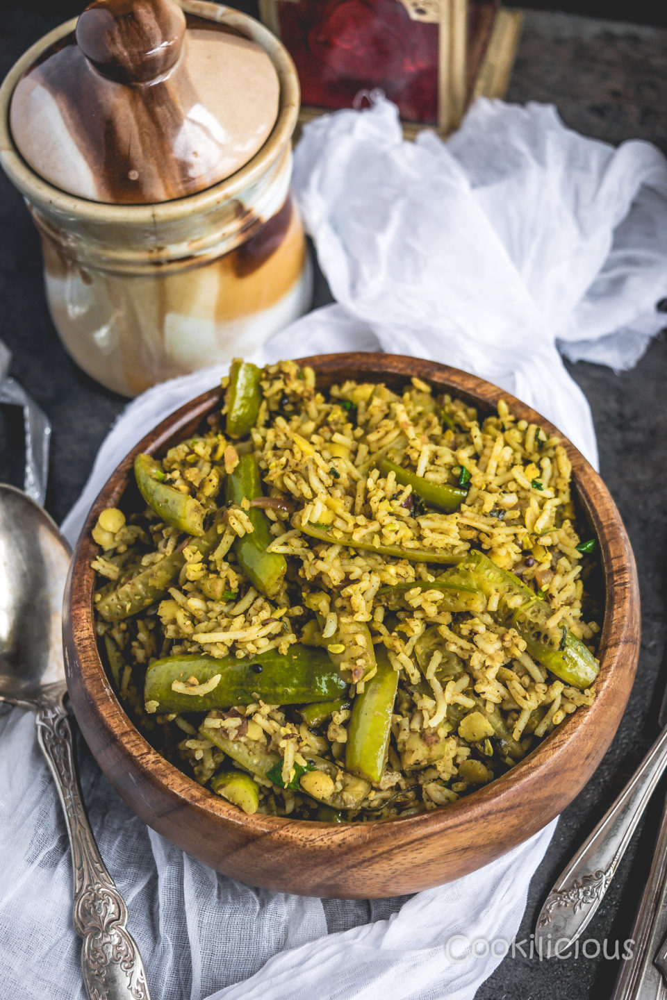 top shot of Tendli Masala Bhaat | Ivy Gourd Masala Rice in a bowl with a pickle jar and spoons in the background
