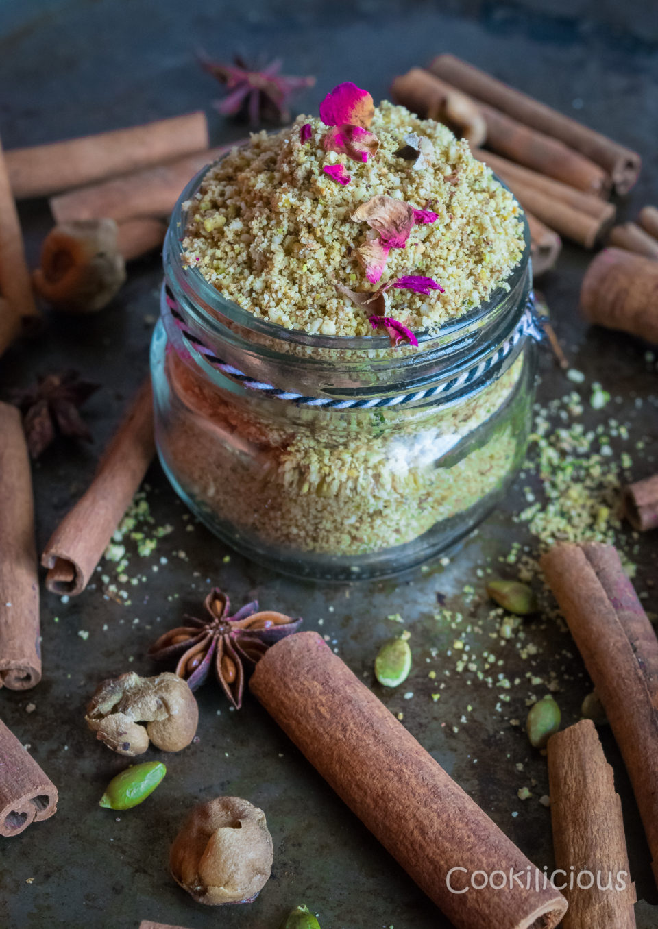 A glass jar filled with milk masala surrounded by cinnamon sticks