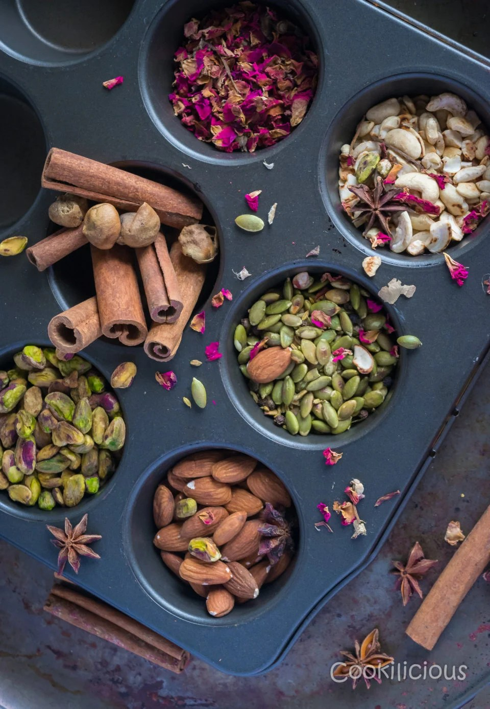 A muffin tray filled with different dry fruits like almonds, cashews, pistachios, cinnamon, pumpkin seeds