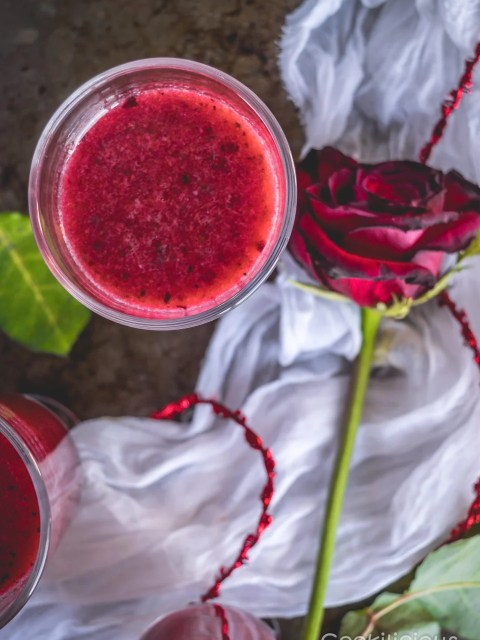 Top view of a glass full of red detox drink along with a red rose by the side.