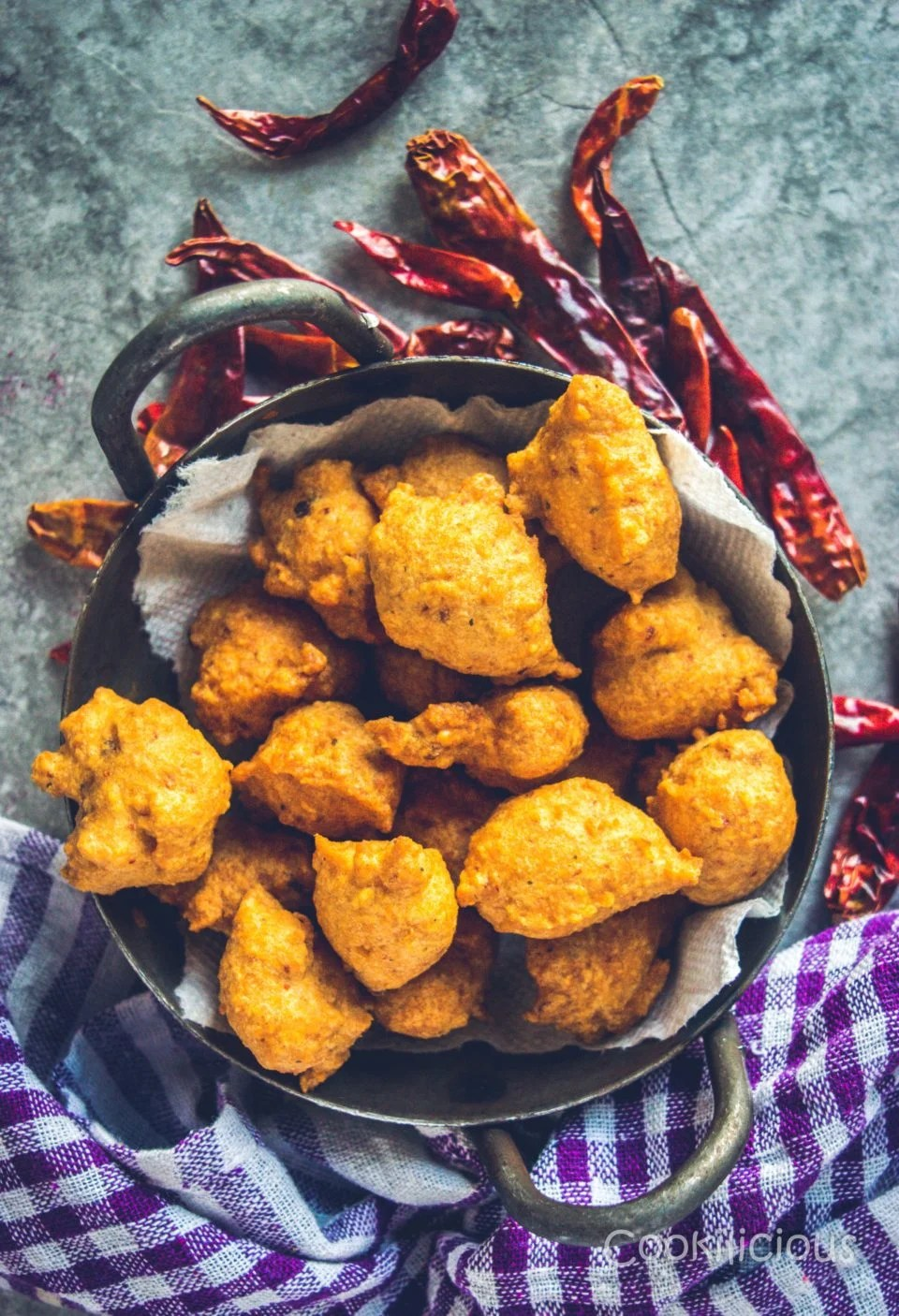 Flat lay shot of South Indian Medu Wada | Lentil Fritters in a kadai with dried red chillies around it.