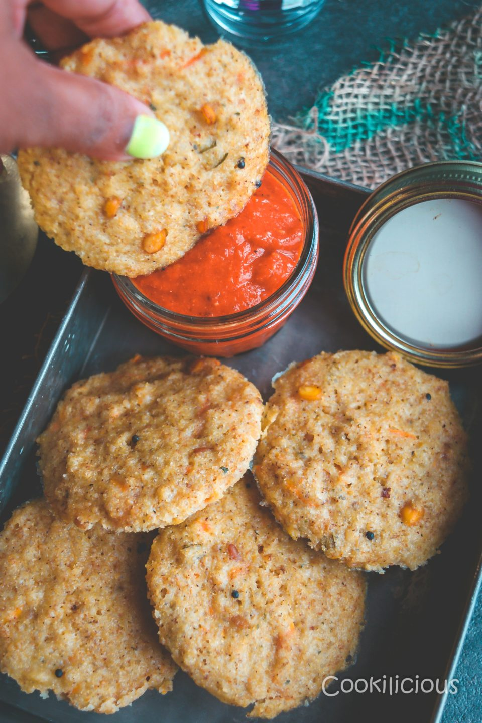 a tray filled with Instant Sweet Potato & Quinoa Idli/Steamed Cakes and one hand dipping an idli in the red chutney