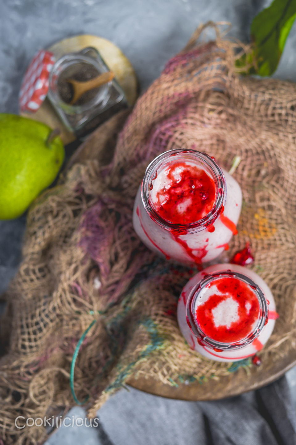 top view of 2 bottles of Healthy Pear & Plums Breakfast Smoothie over a burlap