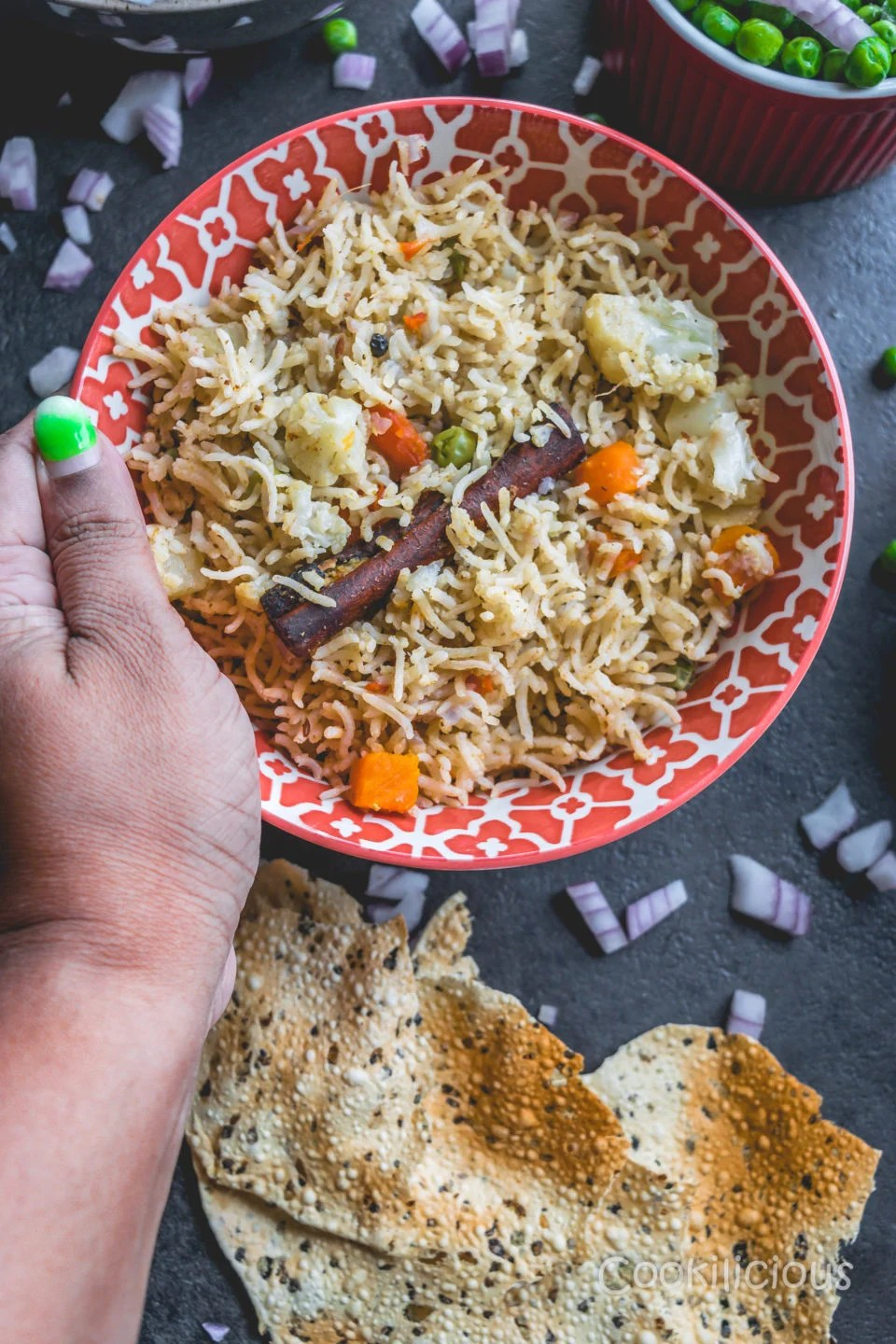 a hand holding a bowl of Vegetable Pulao in Instant Pot