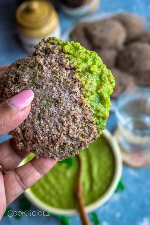 a hand holding a Ragi & Kale Idli