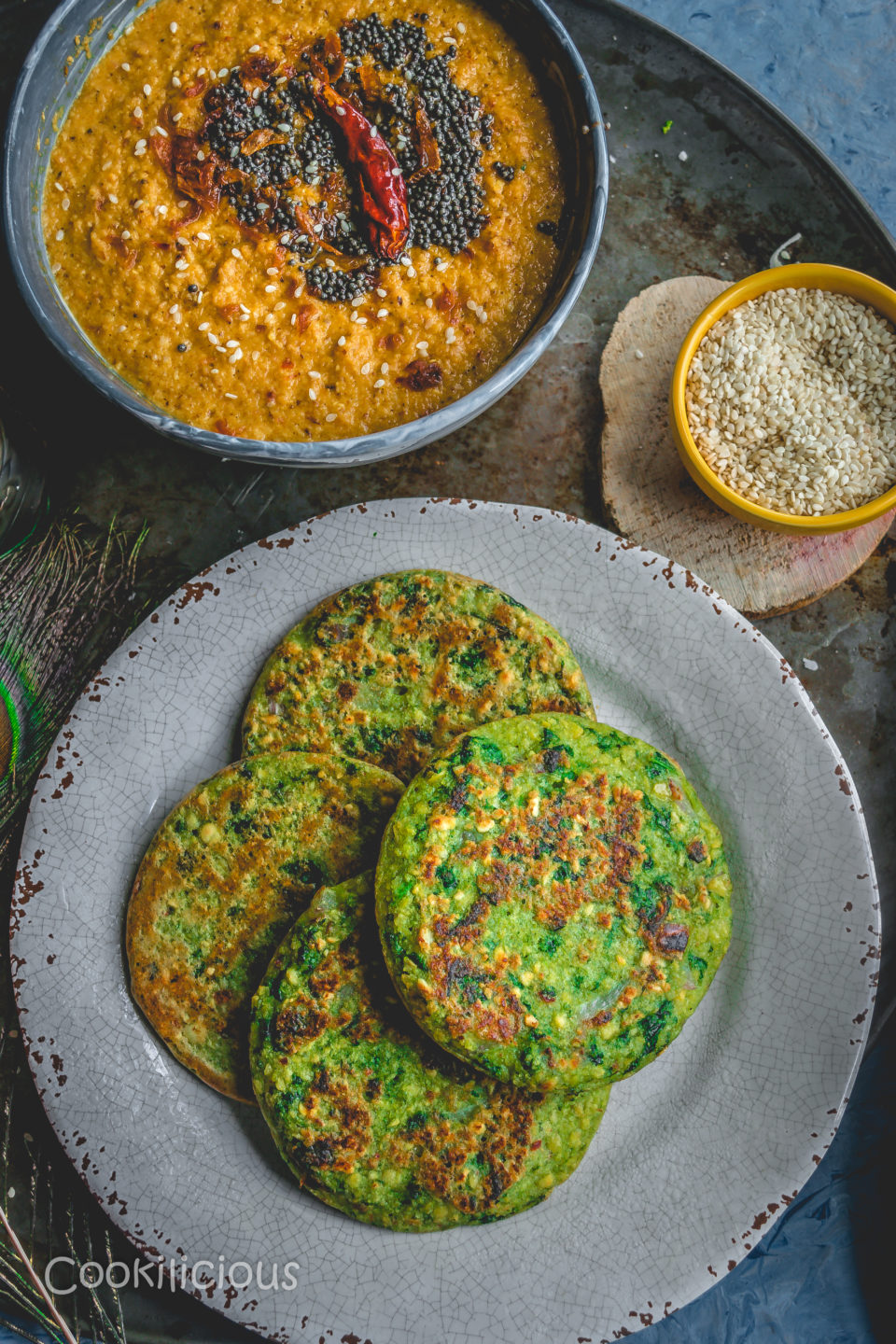 top shot of a plate filled with Kale Adai and orange chutney besides it