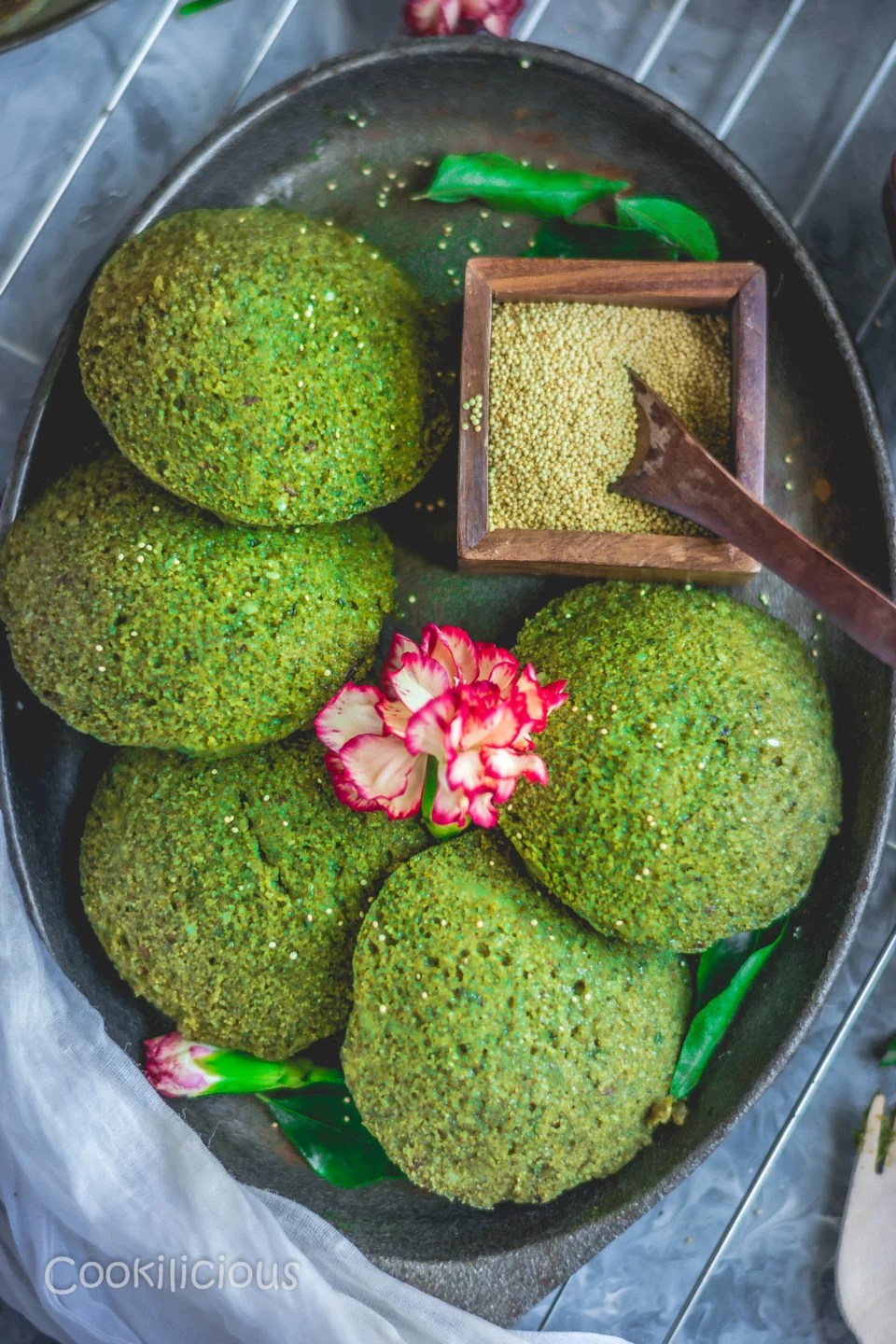 top angle shot of an oval tray with Amaranth Potato Idli and a flower on top along with a wooden bowl filled with amaranth