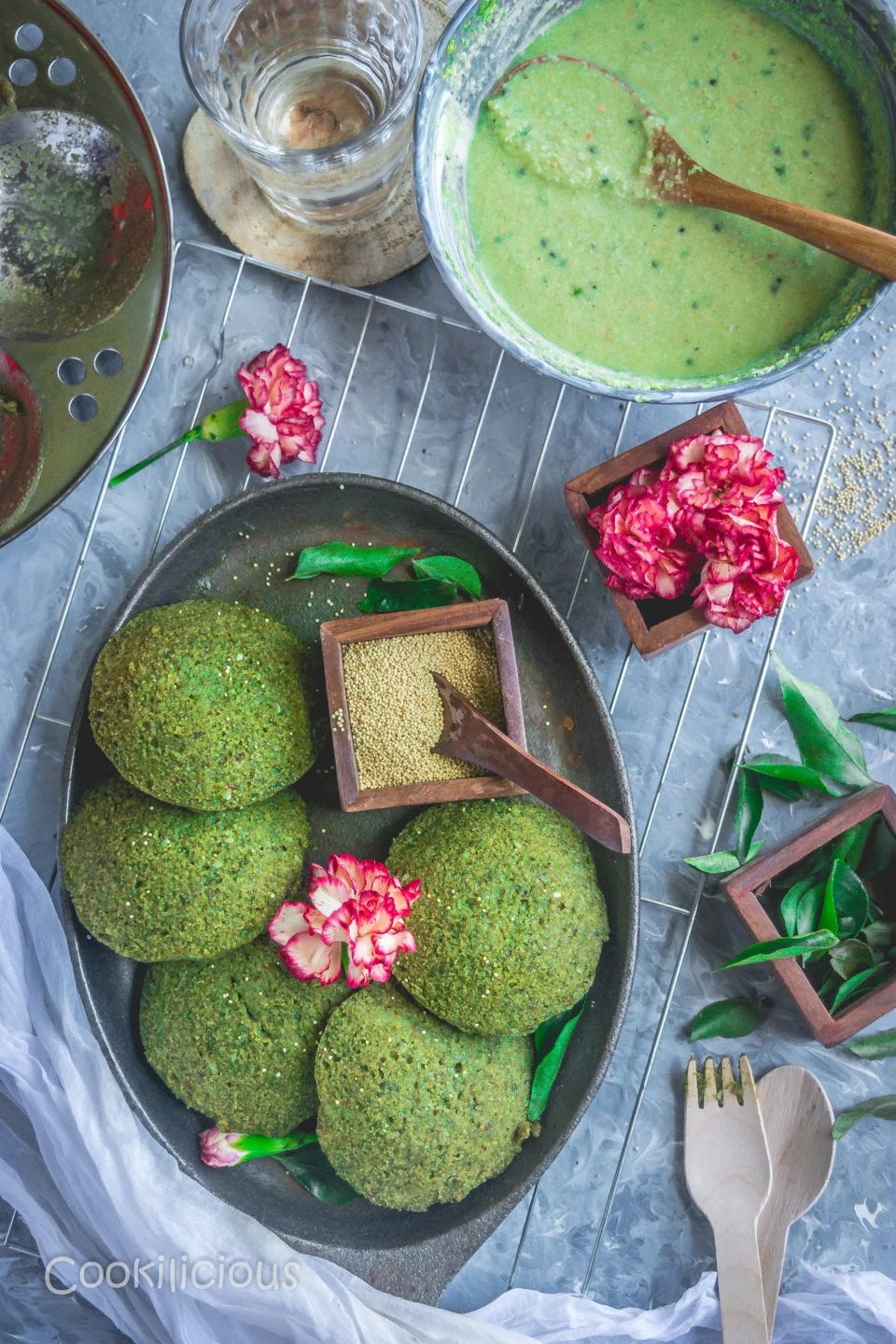 flat lay image of an oval tray filled with Amaranth Potato Idli resting on a wire rack and some red flowers around it. Also a bowl of green chutney in the background