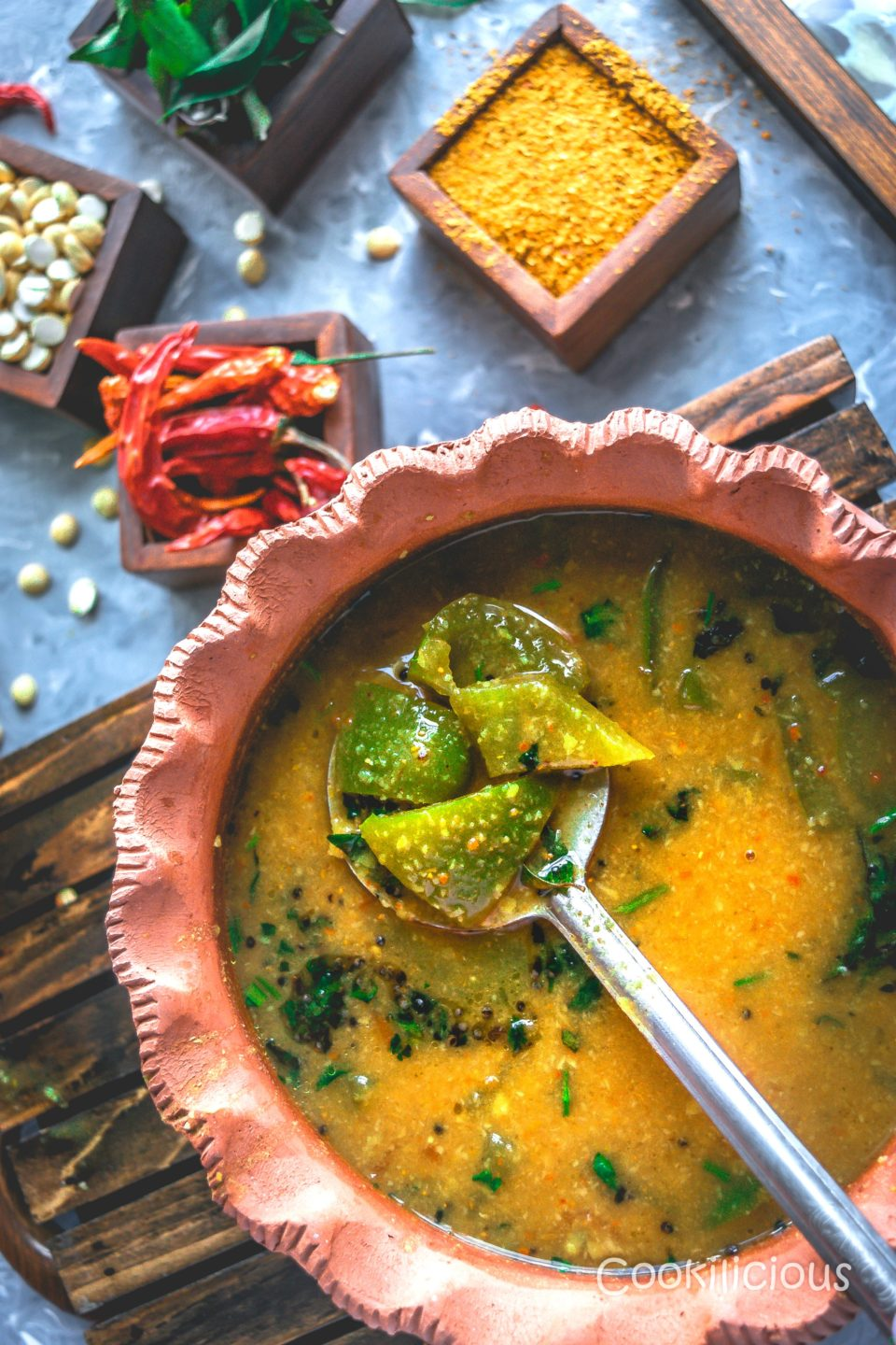 close up shot of the ladle filled with veggies in a pot that's filled with arachuvitta sambhar