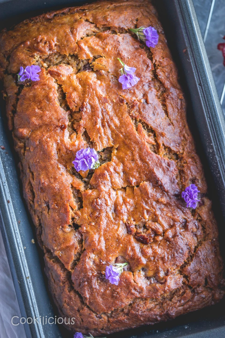 Banana & Strawberry Bread in a loaf pan with purple flowers randomly placed over it