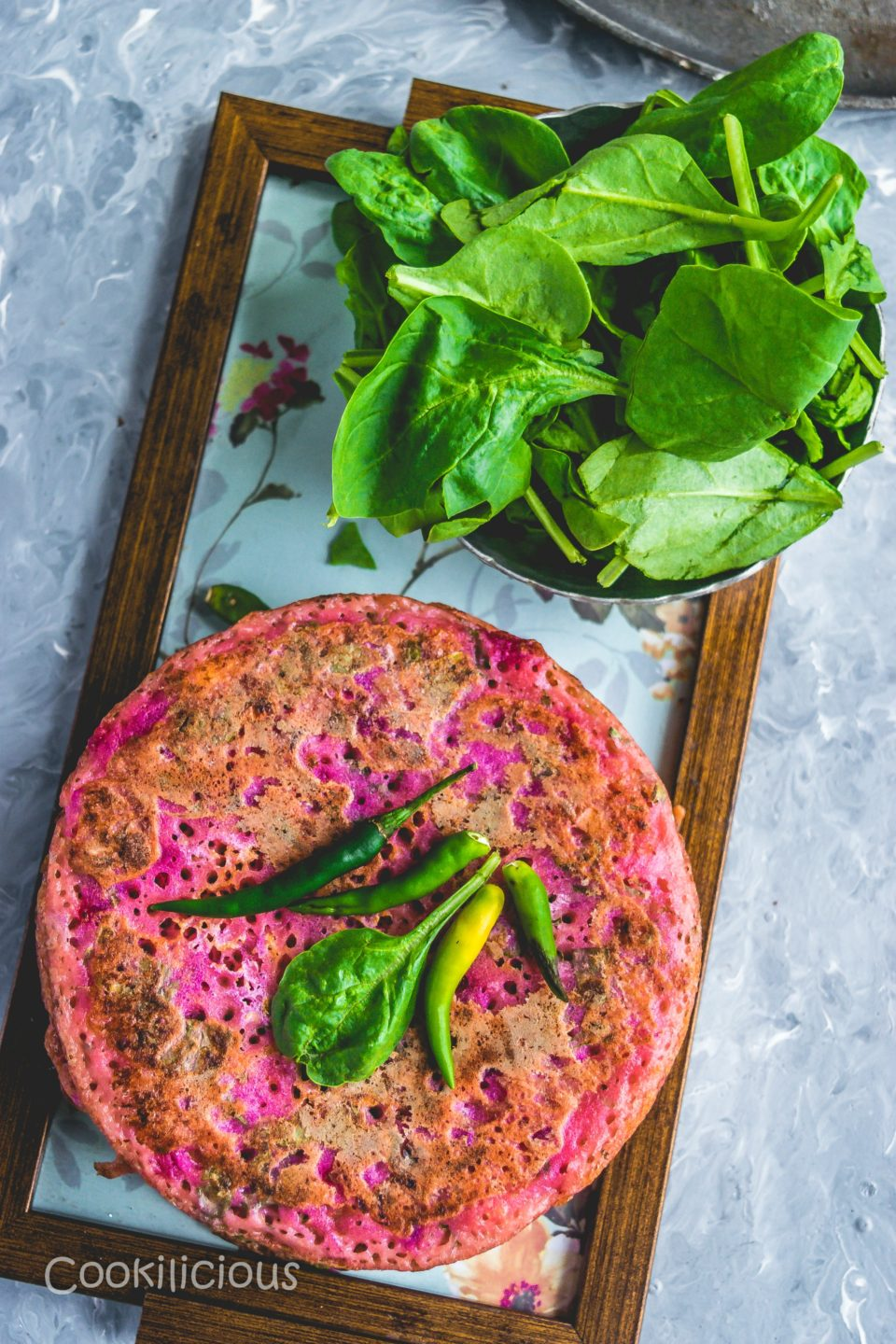 stacked up Pink Uttapam with Beets & Veggies and a bowl of spinach leaves on a tray