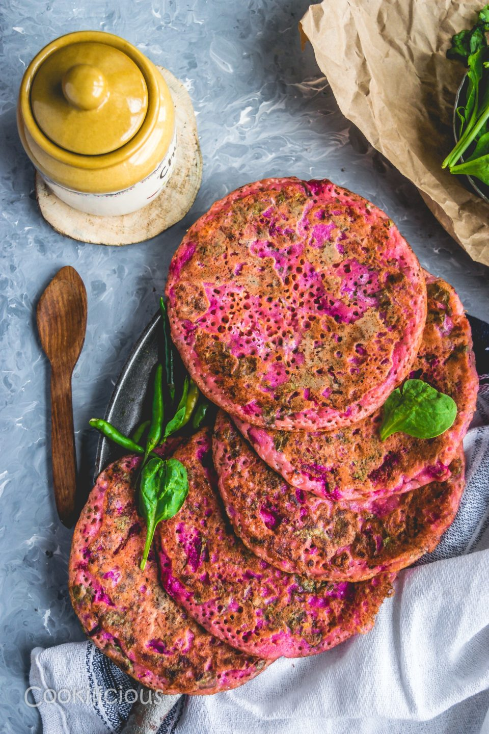 a tray layered with Pink Uttapam with Beets & Veggies with a pickle jar and a wooden spoon around it